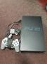 PlayStation 2 met kabels en controller en spellen